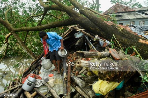 TOPSHOT A man salvages items from his house damaged by cyclone Amphan in Midnapore West Bengal on May 21 2020 The strongest cyclone in decades...
