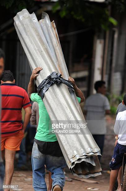 A man salvages the corrugated iron roof of his his already wrecked house on October 24 2008 at El Eden neighborhood on the side of El Picacho hill in...