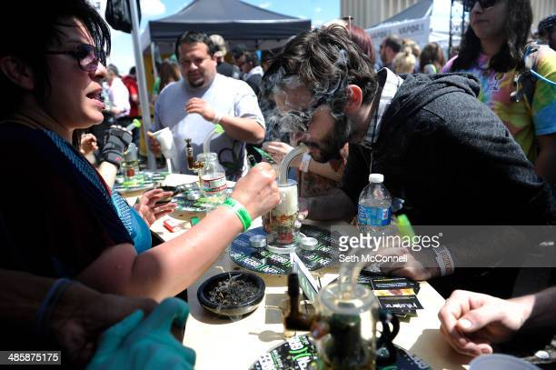 A man samples the marijuana at the Green Solution booth during the High Times Cannabis Cup at Denver Mart in Denver Colorado on April 20 2014 Event...