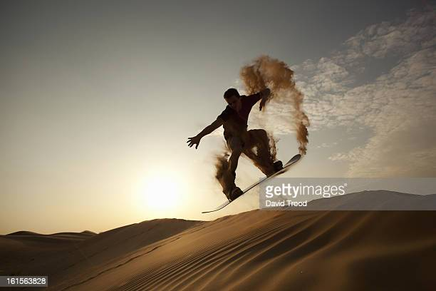 man sand boarding in desert
