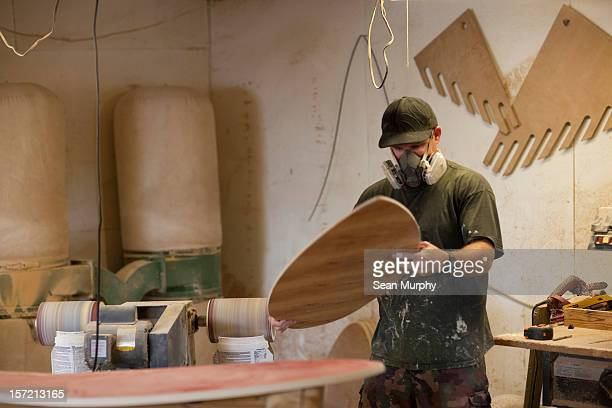A man sanding a wooden skim board