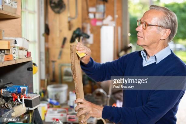 Man sanding wood in garage
