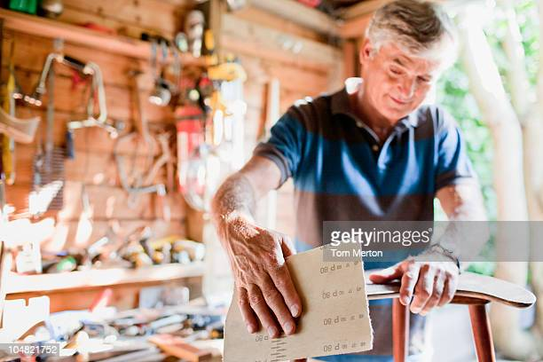 Mann abgeschmirgelten Holz in Workshops