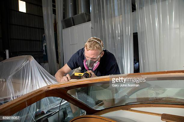 Man sanding woodwork on boat in workshop