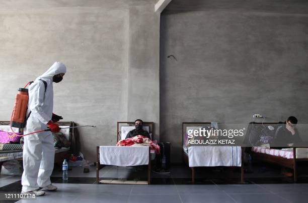 Man sanitises the room as Syrians who returned from Turkey rest at a quarantine facility in the countryside of the town of Jisr al-Shughur, west of...