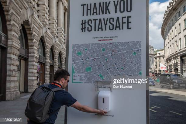 Man sanitizes his hands on Regent Street as non-essential stores re-open for the first time since the nationwide lockdown came into force, on June...