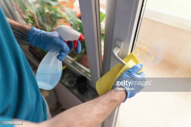 man sanitizing the house during covid-19 threat - prevention stock pictures, royalty-free photos & images