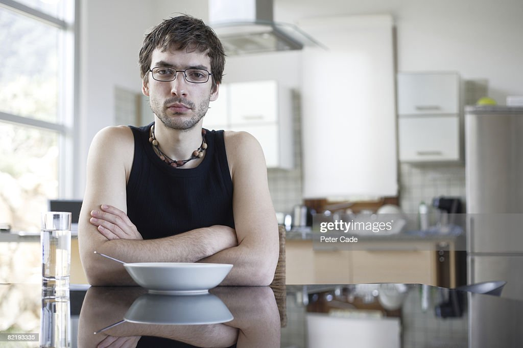 Man sat at table in kitchen : Stock Photo
