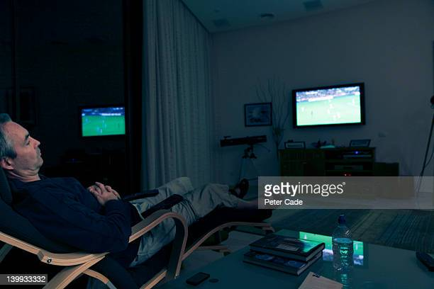 man sat in dark watching football - man cave stock pictures, royalty-free photos & images
