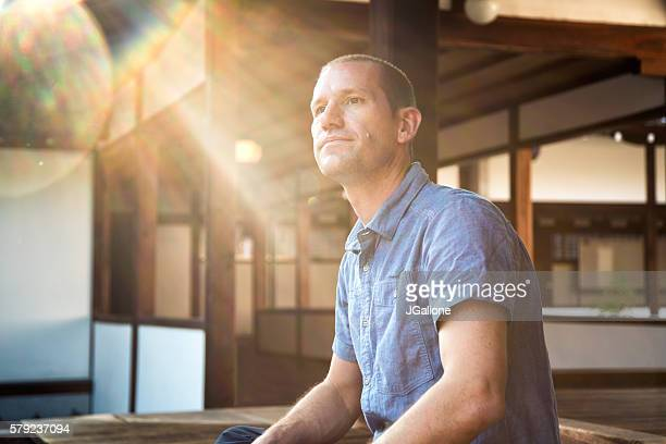 man sat looking thoughtful at a japanese temple - shrine stock pictures, royalty-free photos & images
