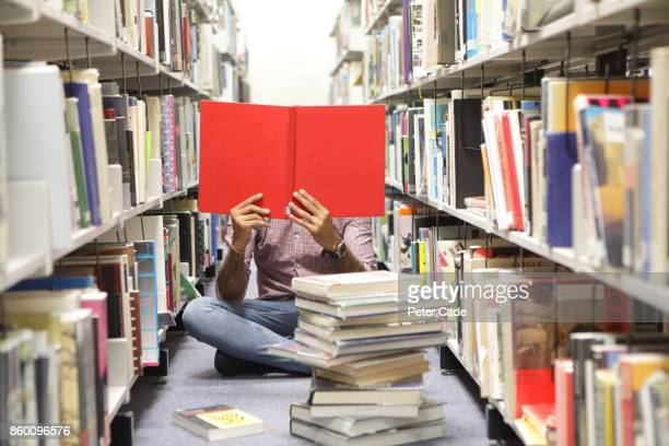 man sat on floor in library reading red book - stack stock pictures, royalty-free photos & images