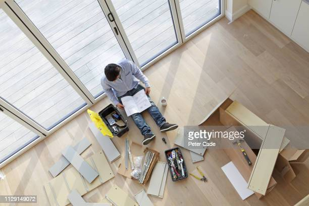 man sat on floor surrounded by flat pack furniture - furniture stock pictures, royalty-free photos & images