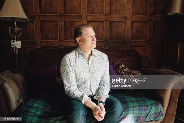 man sat on sofa looking out of window - males stock pictures, royalty-free photos & images