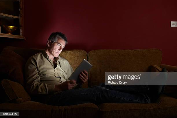 man sat on sofa using digital tablet at night - man cave stock pictures, royalty-free photos & images