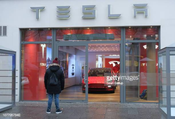 A man satnds outside a Tesla dealership on January 4 2019 in Berlin Germany Tesla is expected to soon begin deliveries of the Model 3 in Europe even...