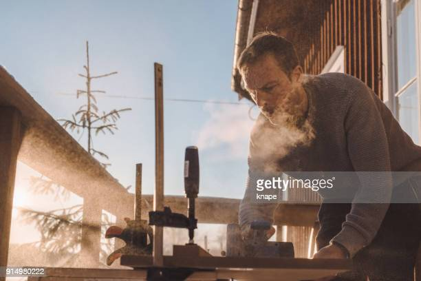 Man sawing wood for home improvement carpentry outdoors in cold winter