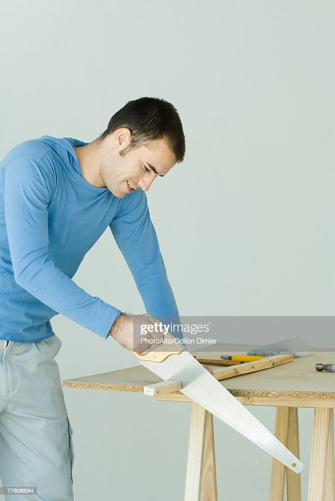 Man sawing wood plank : Stock Photo