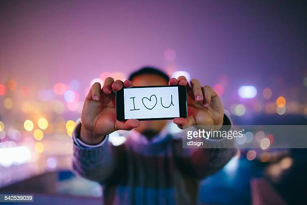 "man saying ""i love you"" with smartphone in city - i love you photos et images de collection"