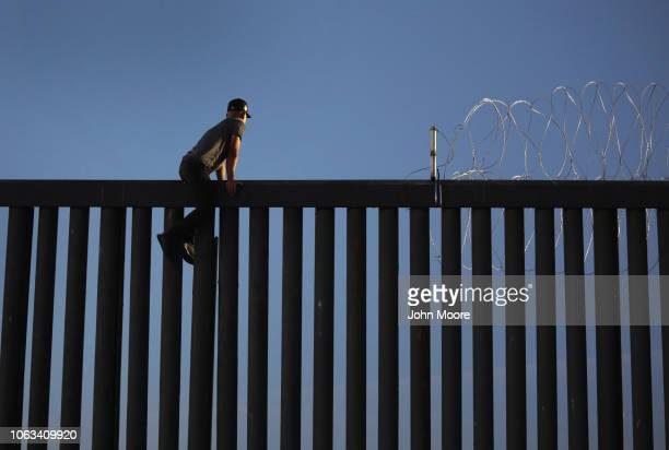 A man scales the USMexico border fence to gaze into San Diego before climbing back into Mexico on November 18 2018 in Tijuana Mexico Parts of the...