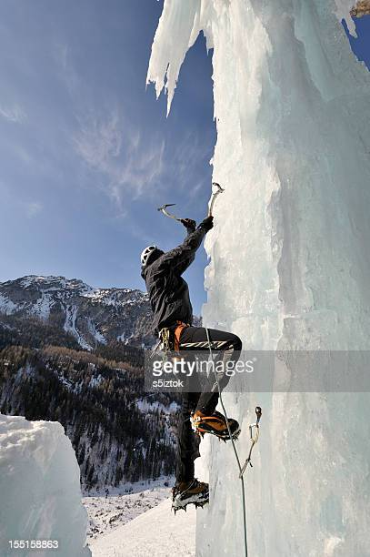 A man scaling a vertical ice cliff