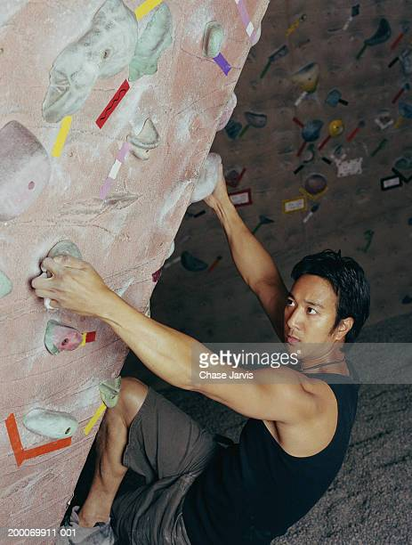 man scaling climbing wall - free climbing stock pictures, royalty-free photos & images