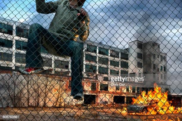 Man scaling wall in gritty urban neighborhood