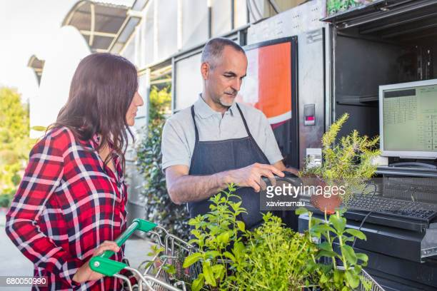 Man scanning bar code on potted plant by woman