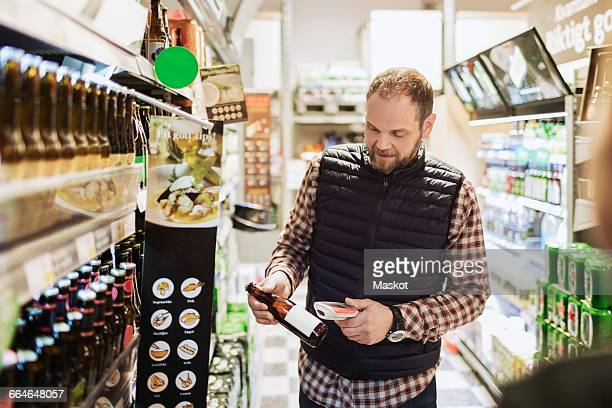 Man scanning beer bottle at grocery store