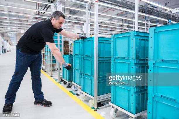 Man scanning boxes on tugger train in industrial hall