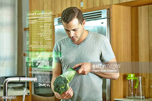 Man scanning broccoli on his phone for food data