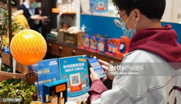A man scans an Alipay QR code to get evouchers at a store on March 27 2020 in Hangzhou Zhejiang Province of China Hangzhou issued 168 billion yuan...