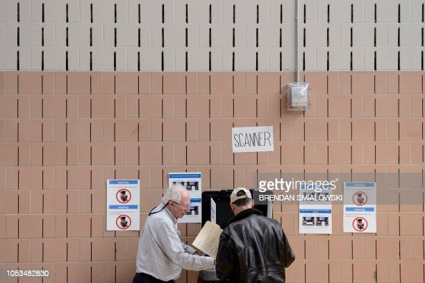 A man scans his ballot at a community center during early voting October 25 2018 in Potomac Maryland two weeks ahead of the key US midterm polls