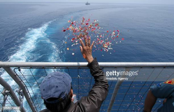 A man scatters flower petals at the sea while relatives and family members of the crashed Lion Air JT 610 passengers gather to hold a mass prayer and...