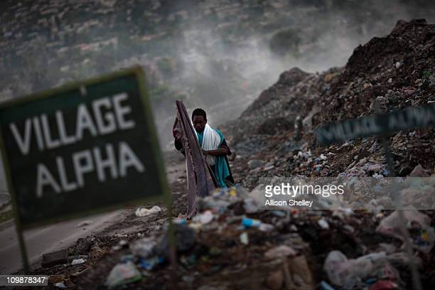 A man scavenges for clothing at an unofficial dump in front of a community called Village Alpha March 8 2011 in PortauPrince Haiti The dump rising 15...