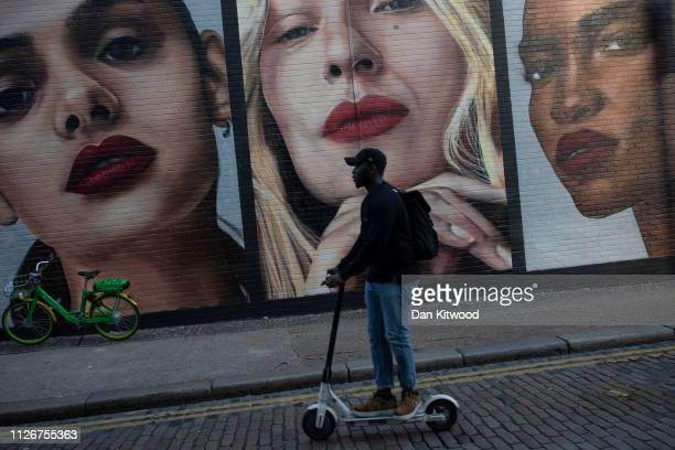 A man scooters past a mural at Shoreditch High Street station near Bethnal Green on February 22 2019 in London England Bethnall Green in East London...
