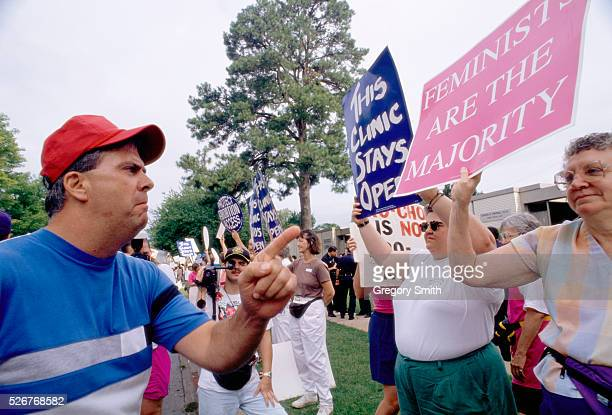 A man scowls as he confronts a prochoice demonstrator outside a pregnancy center in Little Rock One woman's sign reads 'FEMINISTS ARE THE MAJORITY'...