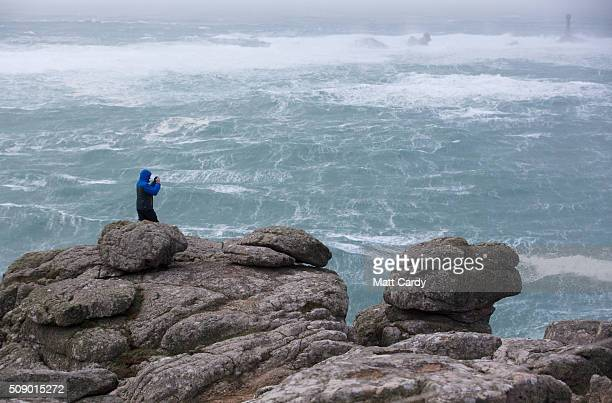 A man scrambles on rocks at Land's End on February 8 2016 in Cornwall England Parts of the UK are currently being battered by Storm Imogen the ninth...