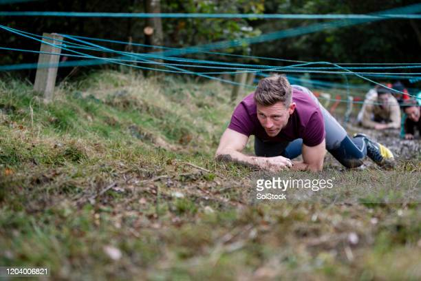 man scrambling on hands and knees in outdoor obstacle course - attending stock pictures, royalty-free photos & images