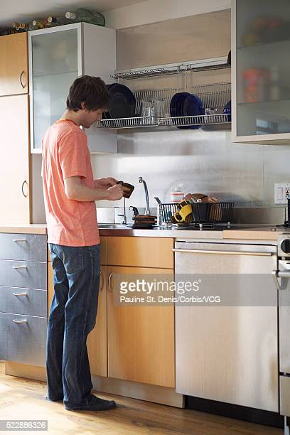 man scraping burned toast - scraping stock photos and pictures