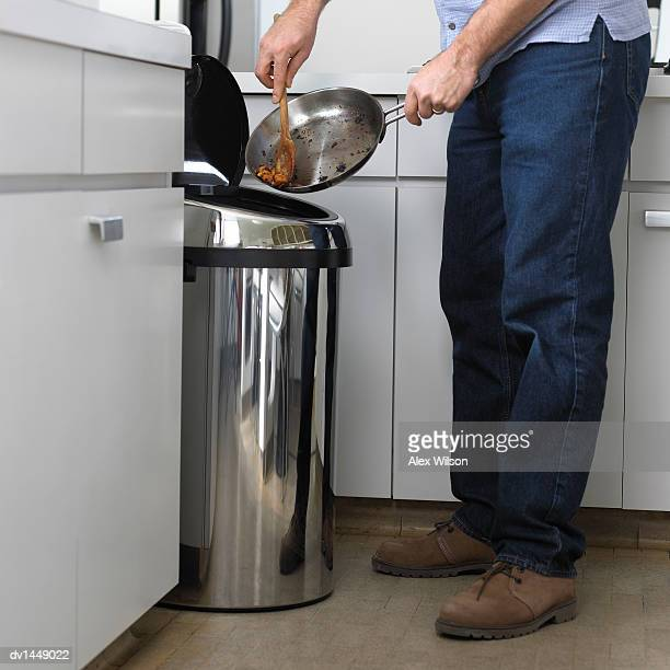Man Scraping Burnt Food into a Bin in a Kitchen