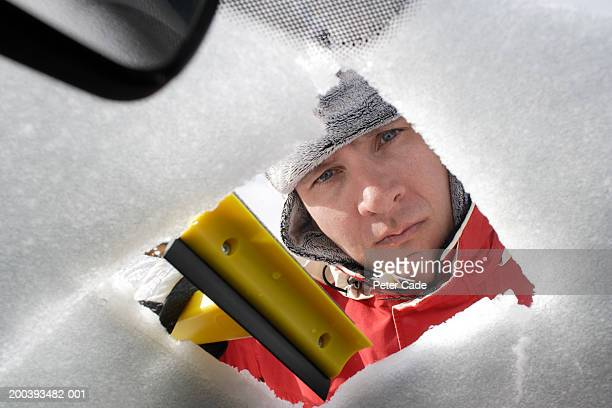 Man scraping snow from car window, view from below, close-up