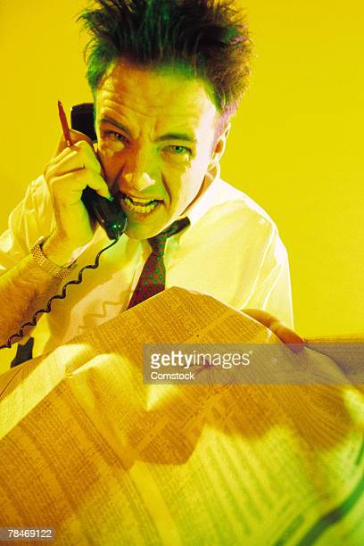 man screaming into telephone and holding stock pages - distressed stock market people stock pictures, royalty-free photos & images