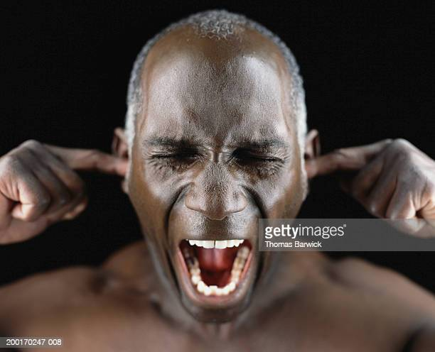 man screaming, putting fingers in ears, eyes closed, close-up - fingers in ears stock pictures, royalty-free photos & images