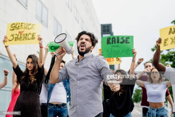 man screaming through megaphone while protesting with people on street in city - protestor stock pictures, royalty-free photos & images