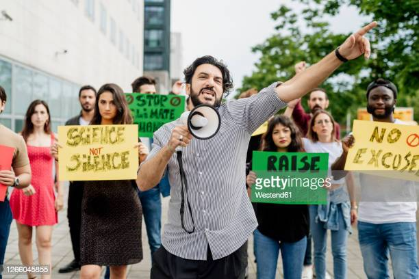 man screaming through megaphone while protesting with people on street - protestor stock pictures, royalty-free photos & images