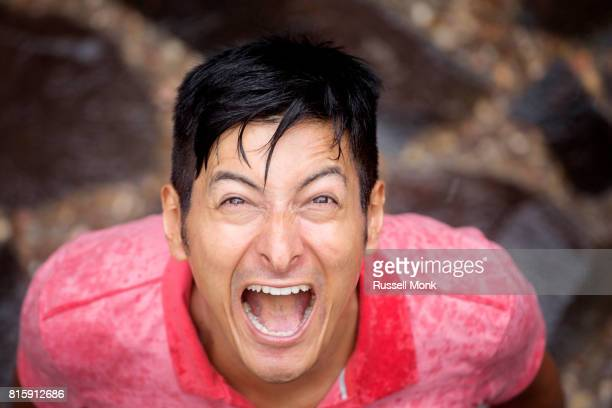 A man screaming with joy during a rain storm