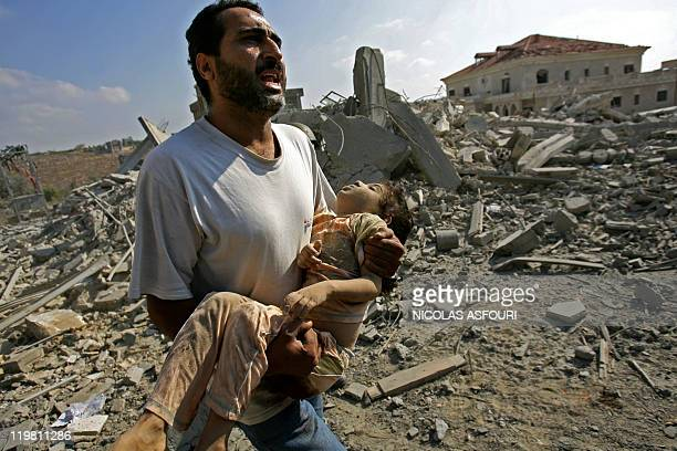 A man screams for help as he carries the body of a dead girl after Israeli air strikes on the southern Lebanese village of Qana 30 July 2006 At least...