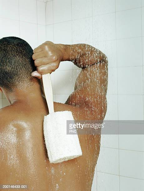 Man scrubbing back with loofah in shower, rear view