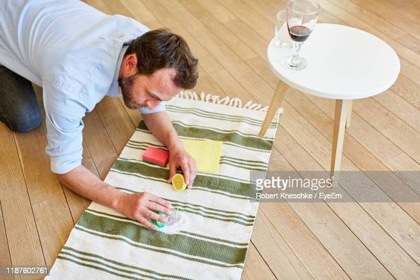 man scrubbing carpet at home - carpet stock pictures, royalty-free photos & images