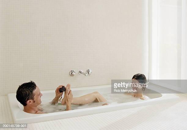 Man scrubbing woman's foot with pumice stone in bubblebath